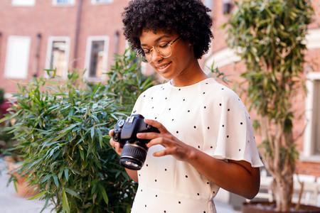 Young woman looking at dslr