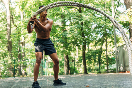 Fit man using two battle ropes