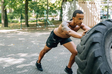 Young muscular man pushing tyre