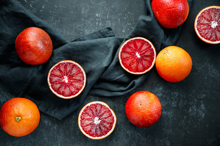 Flat lay food composition with blood oranges on a dark blue background
