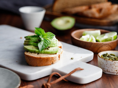 Avocado toast with pepitas and fresh basil on a white marble cutting board Home cooking healthy eating concept