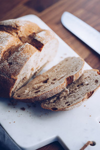 Cutting rye bread loaf and a knife on a white marble cutting board