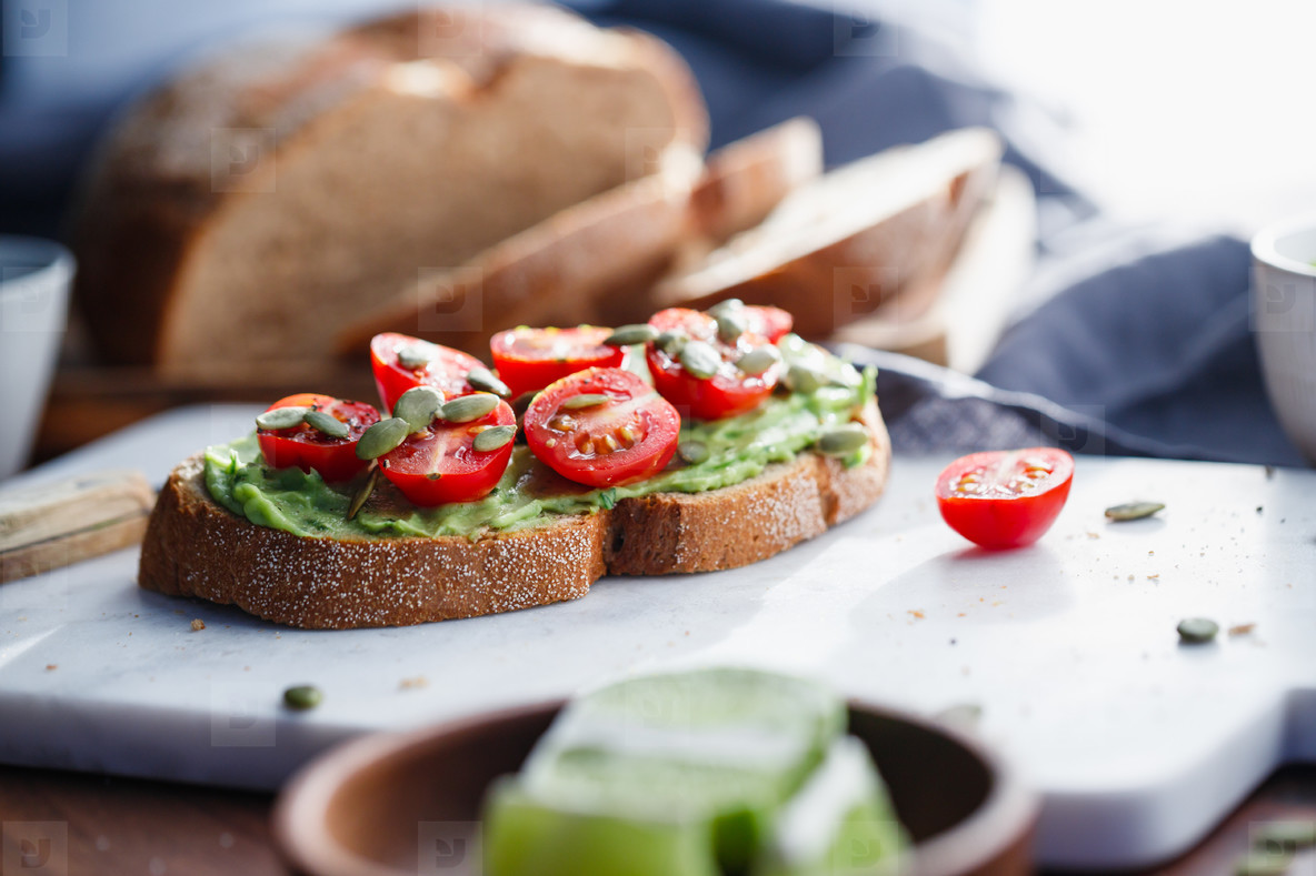 Avocado toast with cherry tomatoes and pepitas on a white marble cutting board  Home cooking  healthy eating concept