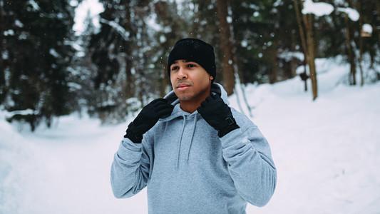 Male runner holding hood