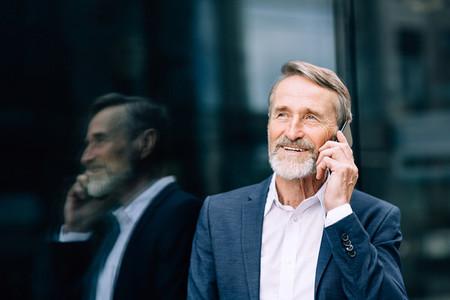 Smiling senior man making call