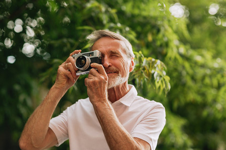 Senior man making photographs