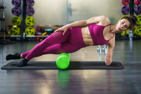 Woman relaxing her leg muscles with a green foam roller