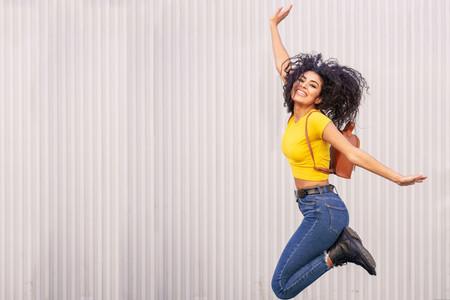 Happy Arab woman jumping in urban background