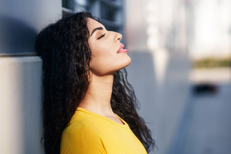Arab woman with eyes closed in urban background