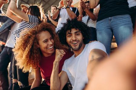 Couple of spectators taking selfie in stadium