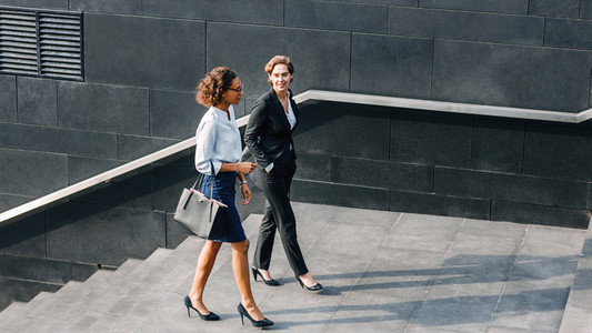 Two women in office wear walking