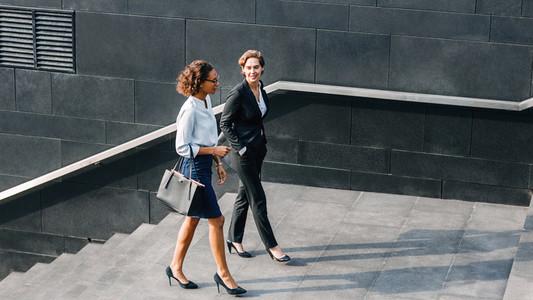 Two women in office wear walking