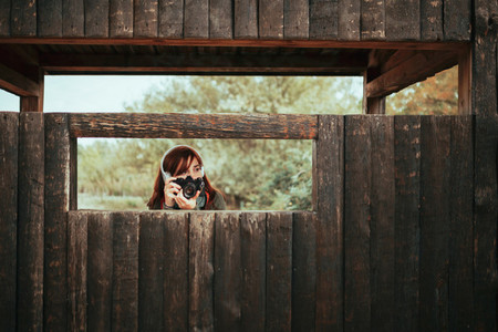Young woman taking photos from wooden hut in the forest