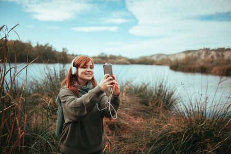 Young woman taking a selfie with her smartphone near a lake