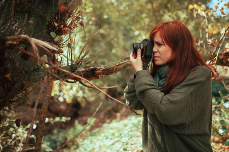 Young woman taking photos in the forest with an old camera