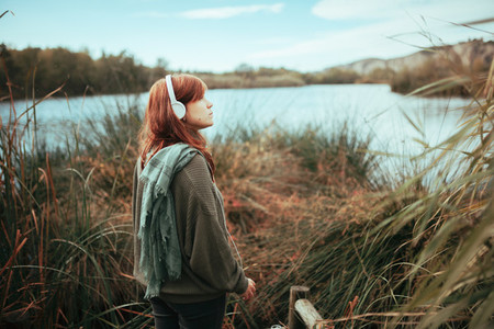 Young redhead woman walking to the lake shore with headphones