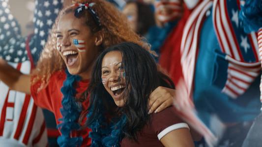 Group of American soccer fans cheering in fan zone