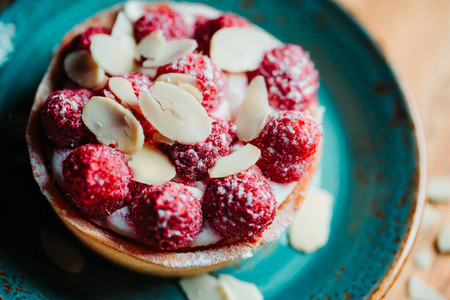 Raspberry tartlet dessert with almond flakes on a blue ceramic plate  Close up view
