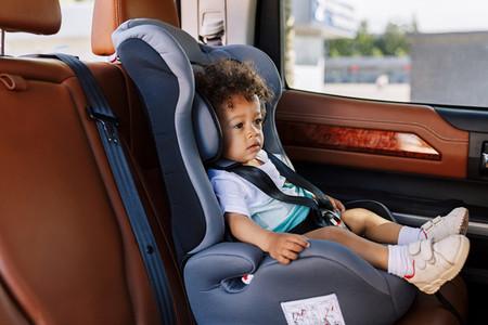 Curly little boy sitting in seat