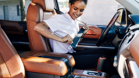 Smiling woman sitting in her car