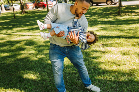 Young father carrying happy son
