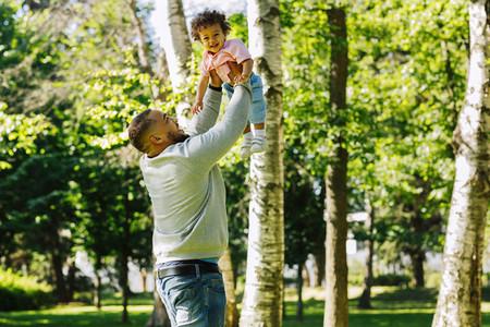 Man lifting his son high