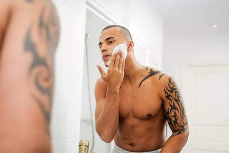 Reflection of man applying cream