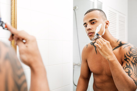 Mixed race person shaving face