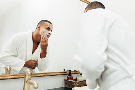 Handsome man applying a cream
