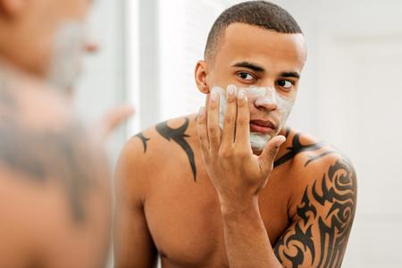 Young man applying cream
