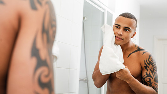 Young handsome man drying face