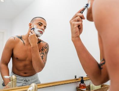 Young man shaving his cheek