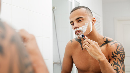 Mixed race person shaving