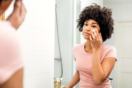 Young woman in bathroom looking