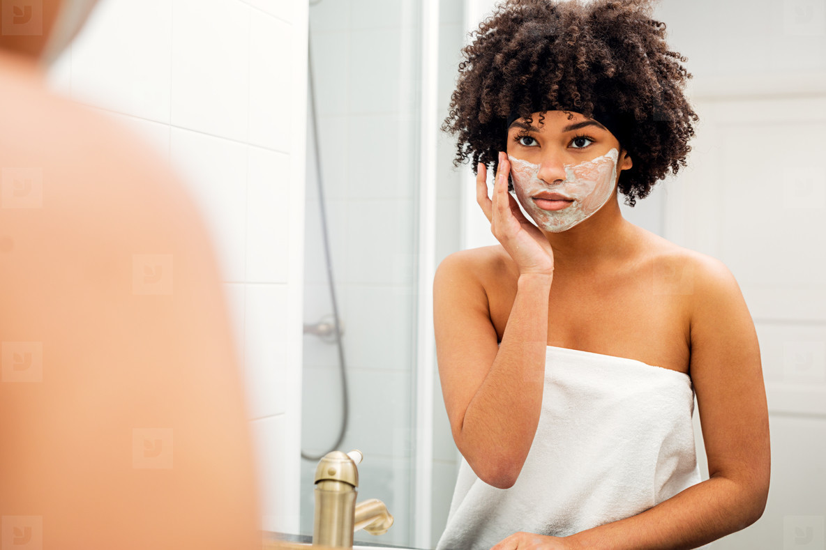 Woman applying facial mask