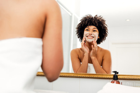 Smiling woman applying cream