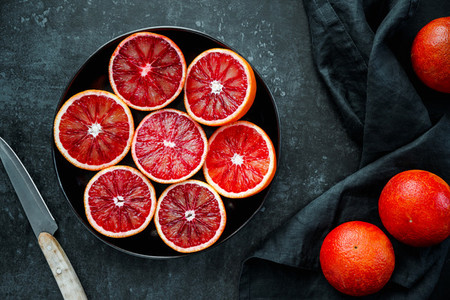 Cutted blood oranges in a plate on a dark blue background