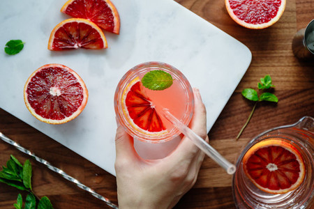 Refreshing cold summer cocktail with blood orange and mint on a marble tray Top view flat lay composition