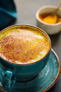 Closeup view of turmeric latte cup on a textured dark background