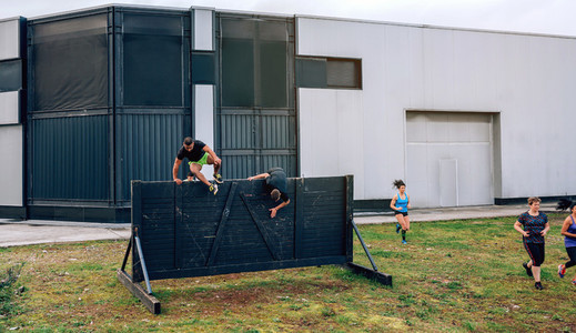 Participants in obstacle course running and climbing wall