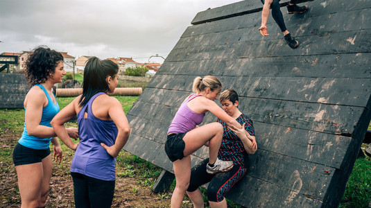 Female participants in obstacle course climbing pyramid obstacle