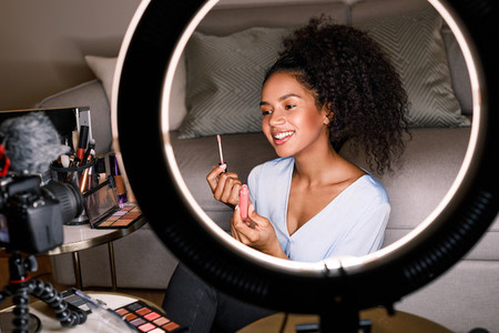 Smiling vlogger showing lipstick