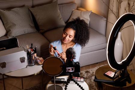 Beauty vlogger holding lipstick