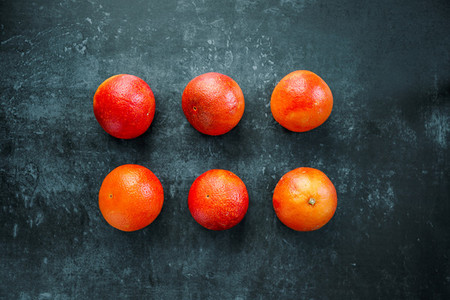 Six blood oranges on a dark blue background flat lay food composition top view