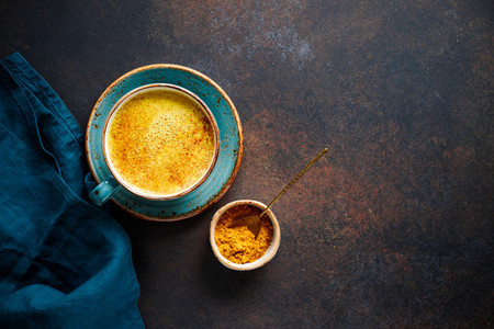 Top down view of turmeric latte cup on a textured dark background