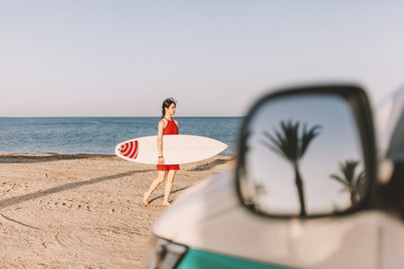 Young woman with surfboard on the beach near a van