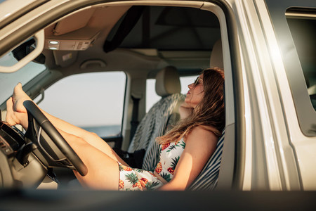 Woman sitting in the drivers seat in a van with mini skirt