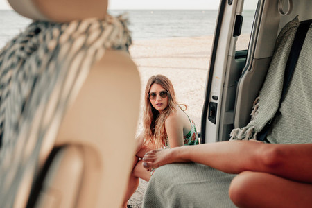 Two young women inside de van near the beach
