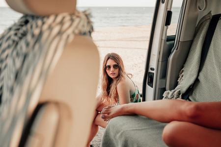 Two young women inside de van near the beach