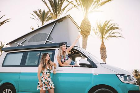 Two young women having fun in her van near the beach